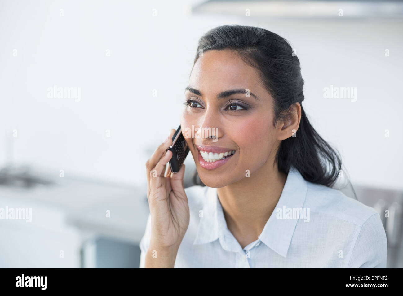 Gleeful young woman phoning with her smartphone - Stock Image