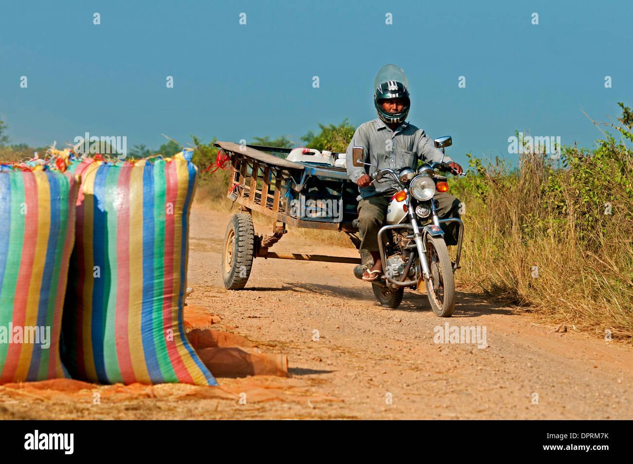 Man on motorbike on a country road near Battambang passing rice bags, Battambang, Cambodia - Stock Image