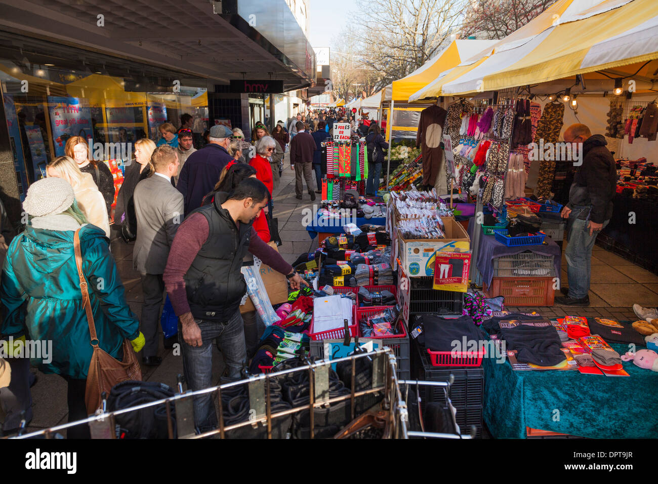 Shoppers browsing market stalls in town centre high street. - Stock Image