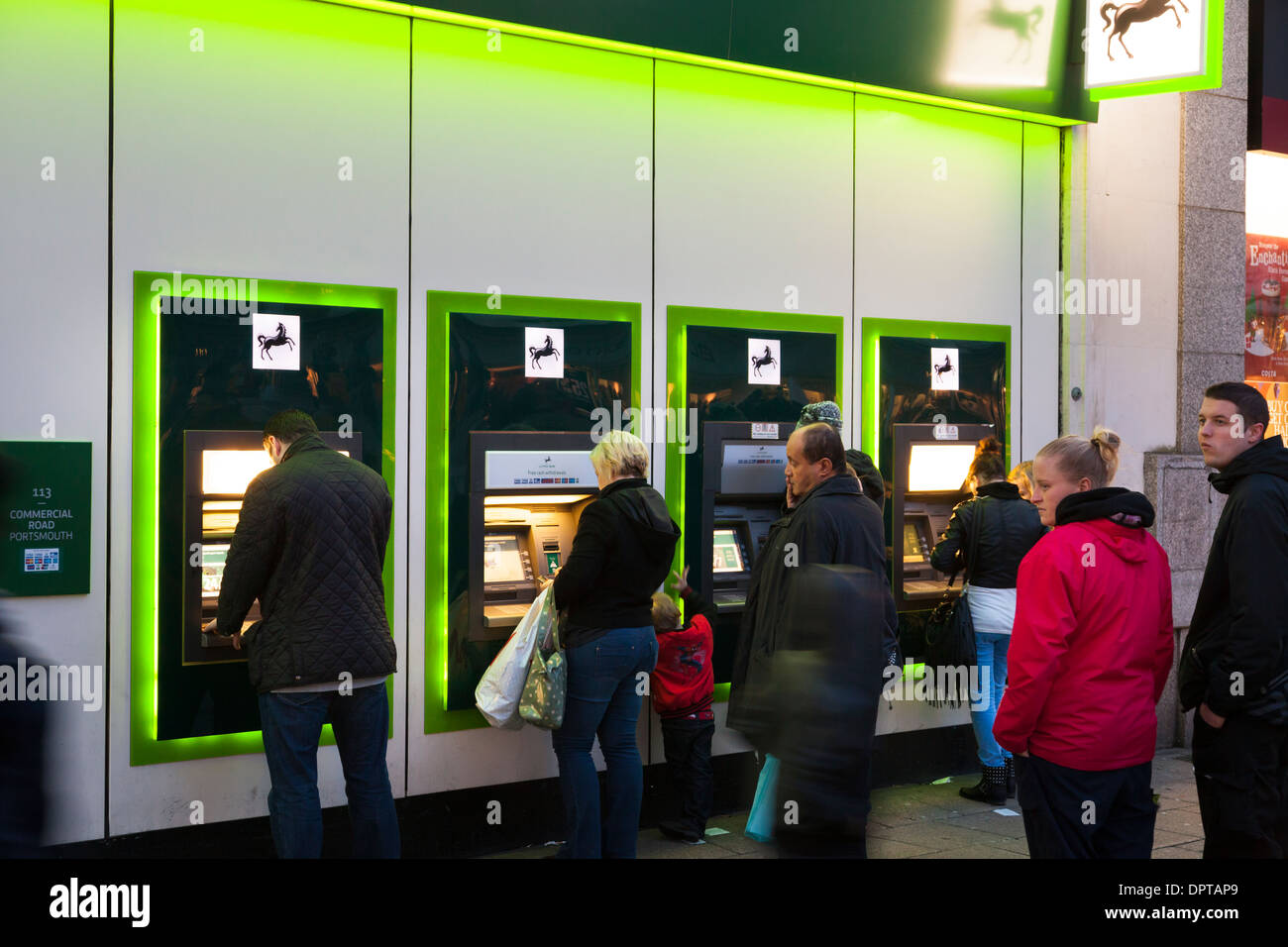 Customers using Lloyds Bank ATM machines after dark. - Stock Image