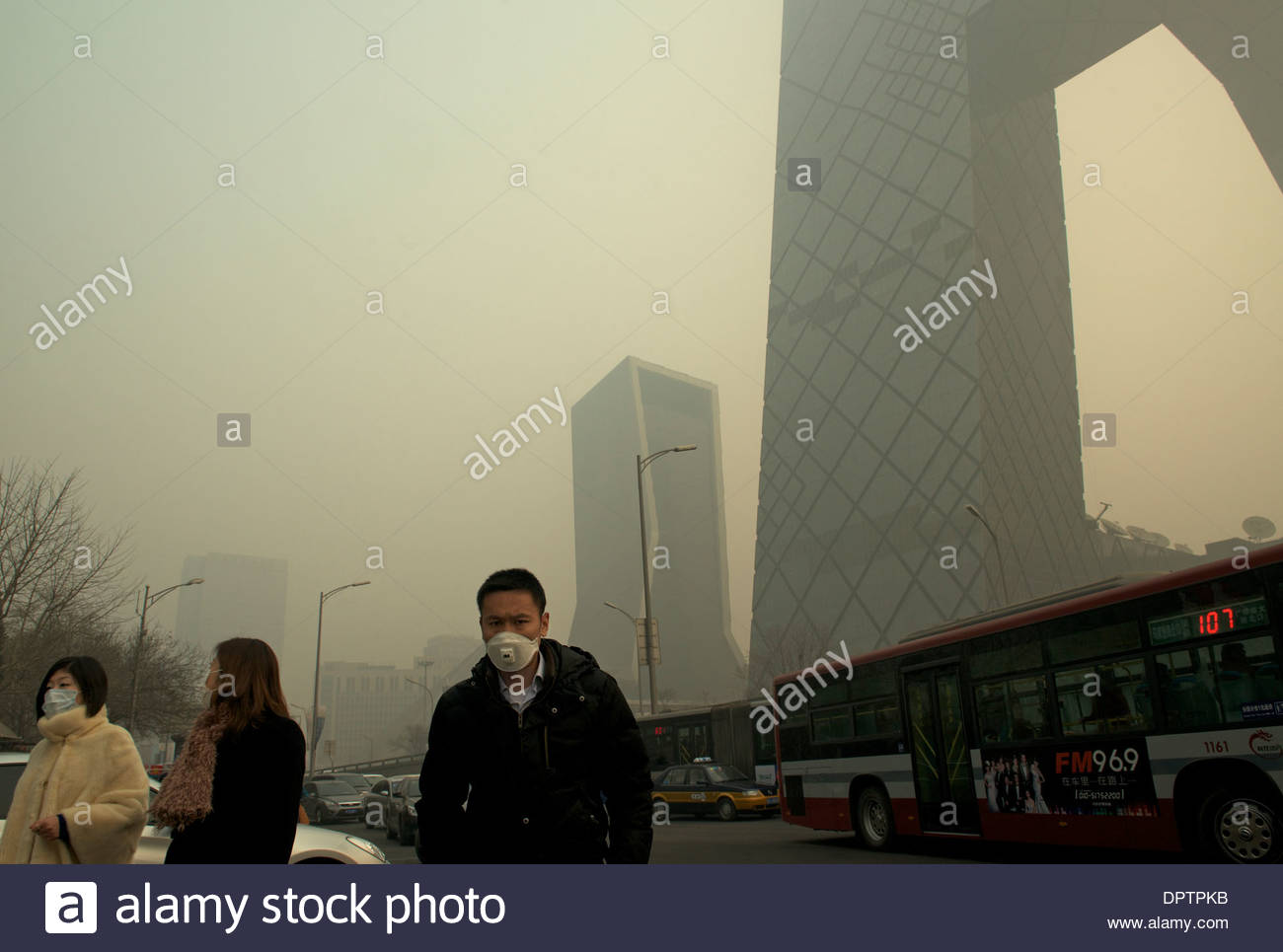 People wear masks past China CCTV (China Central Television) headquarters in strong air pollution that covers Beijing. 2014 - Stock Image