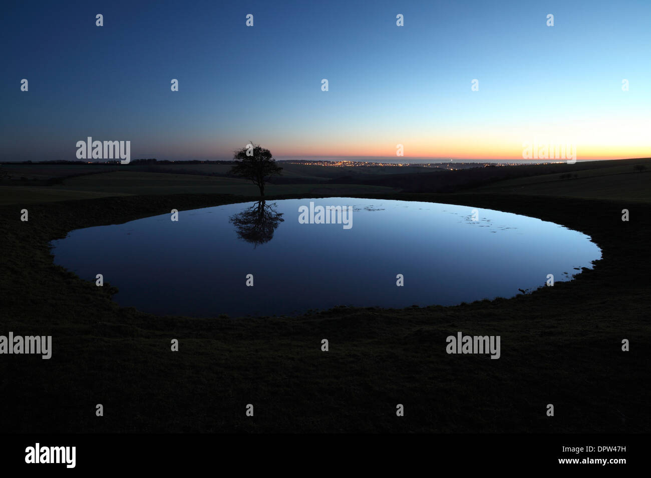 Dew pond on the South Downs at dusk. The sea and the lights of Brighton are just visible in the background. - Stock Image