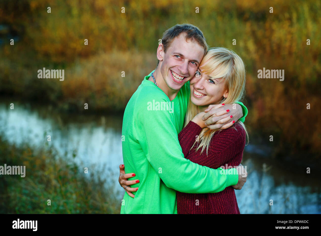Young couple tenderly and lovingly embrace each other on banks of river - Stock Image