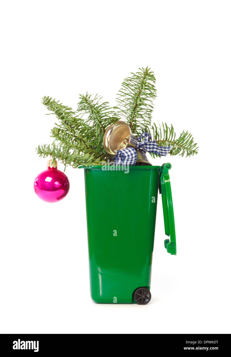 Christmas decorations in the green wheelie bin against white background - Stock Image
