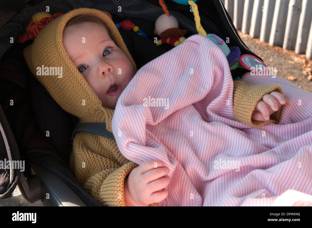 baby girl sitting in her pram looking at the camera and making faces