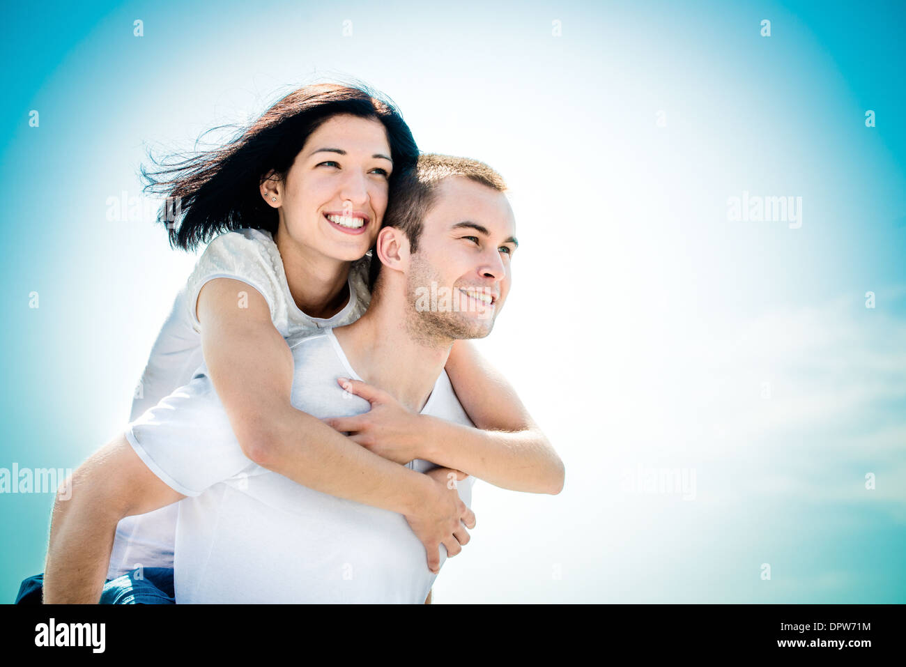 Young couple looking to bright future - happy woman embracing her love around neck - Stock Image