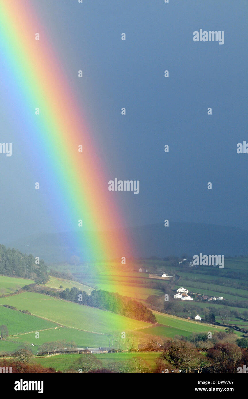 Aberystwyth, Wales, UK. 16th Jan, 2014. A rainbow frames the view of the Cambrian Mountains behind Capel Dewi, Aberystwyth, Wales, UK as showers sweep across the valley. Credit:  John Gilbey/Alamy Live News - Stock Image