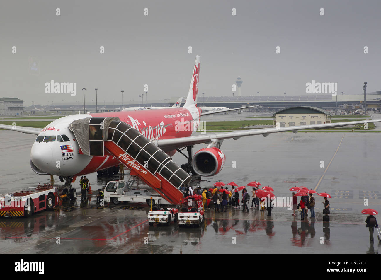 Passengers boarding Air Asia airlines flight using staircase in the rain, with red umbrellas provided by the airline - Stock Image