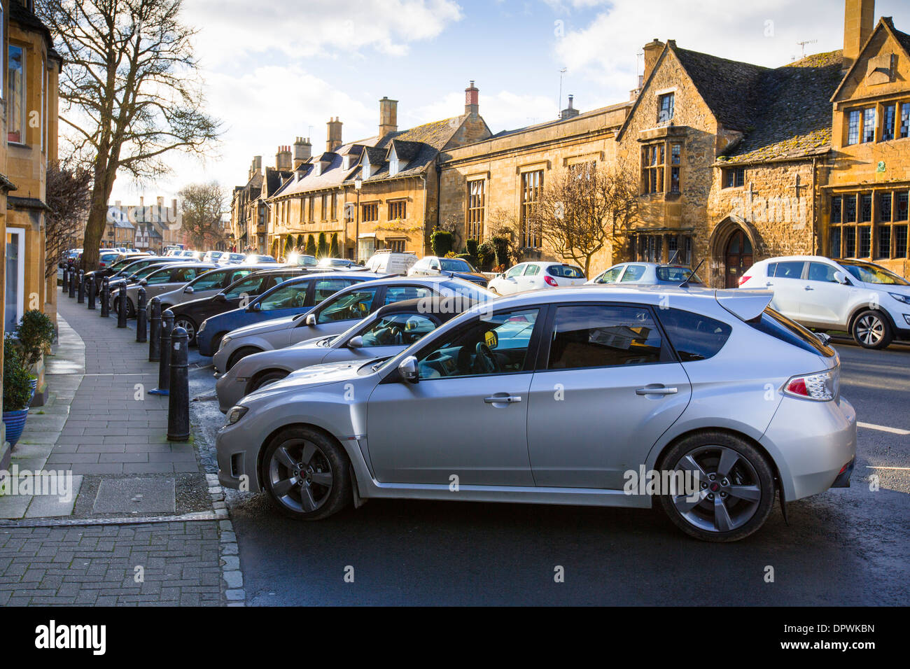 Vehicles parked in the High Street in Chipping Campden, Gloucestershire. - Stock Image