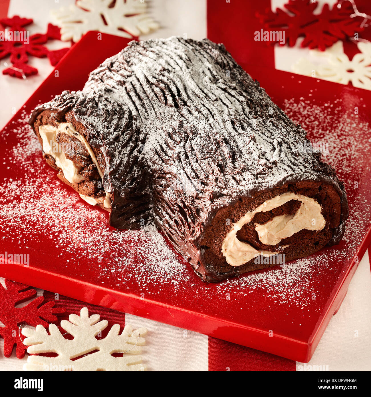 Yule log chocolate sponge vanilla cream Christmas traditional red plate icing sugar dusting snow flake decoration - Stock Image