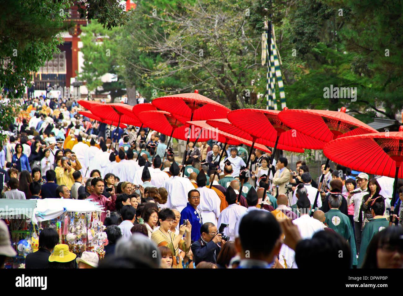 Bright red parasols carried at a Buddhist procession, at Todaiji Temple, Nara - Japan. - Stock Image