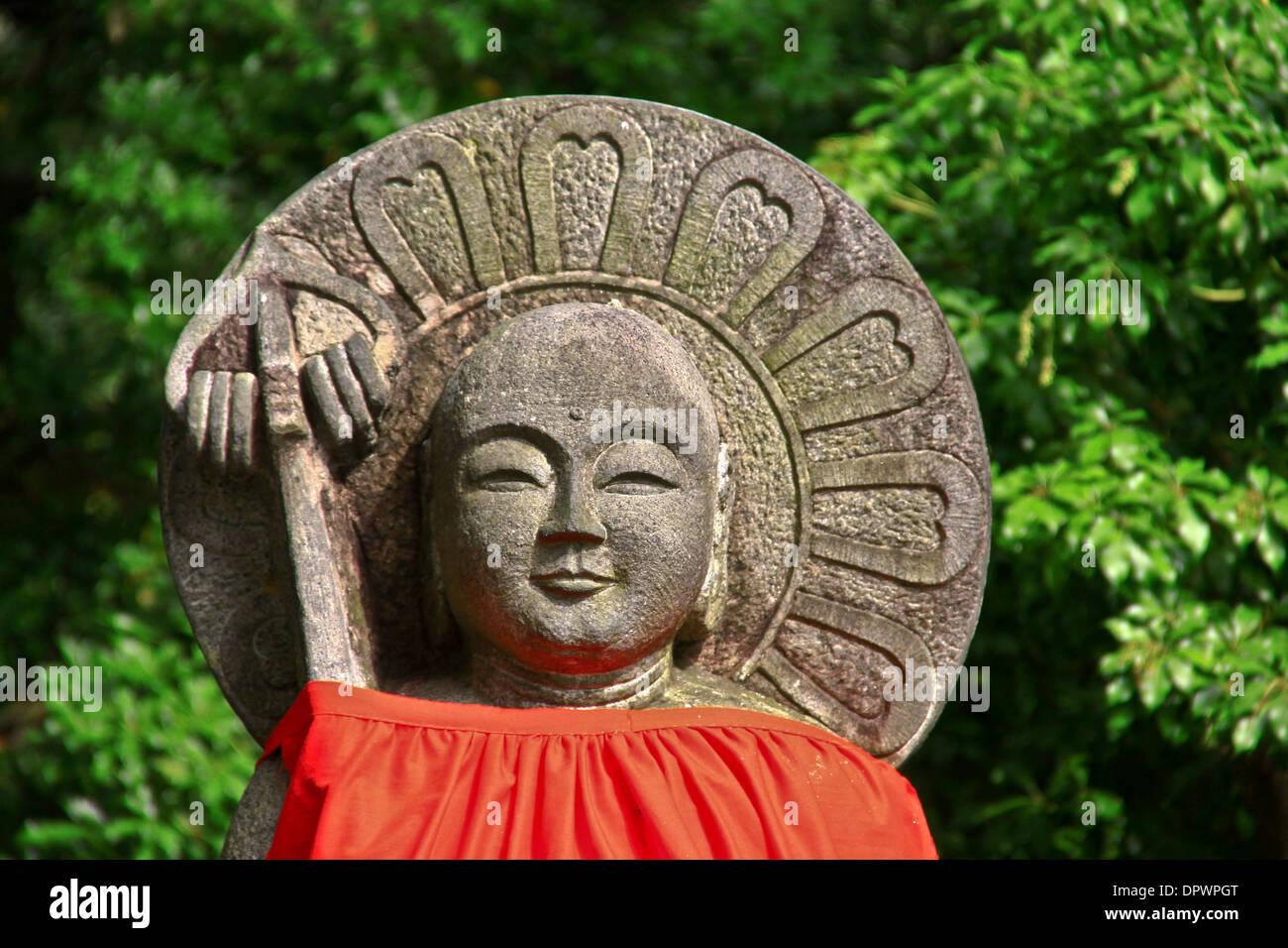 An Ojizo-sama statue, dressed in a red bib, near Todaiji Temple, Nara Park, Japan. - Stock Image