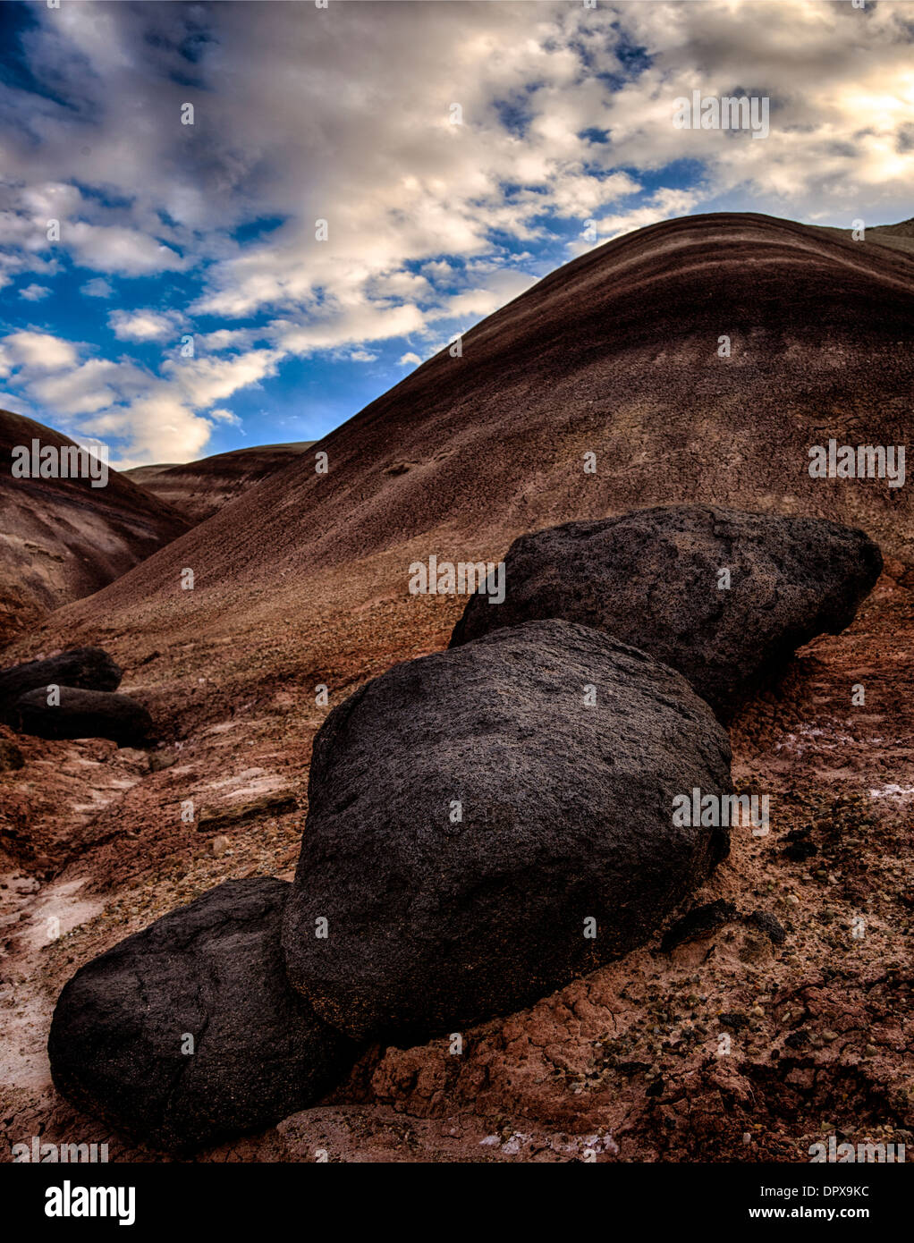 Lava boulders and colorful clay hills do the landscape along the Fremont River near Cainville Utah. - Stock Image