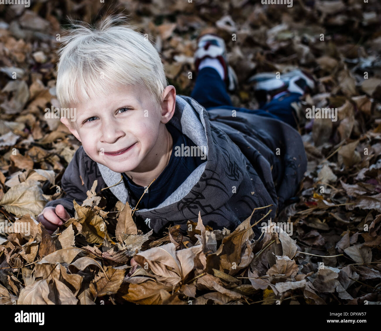 Boy playing with leaves - Stock Image