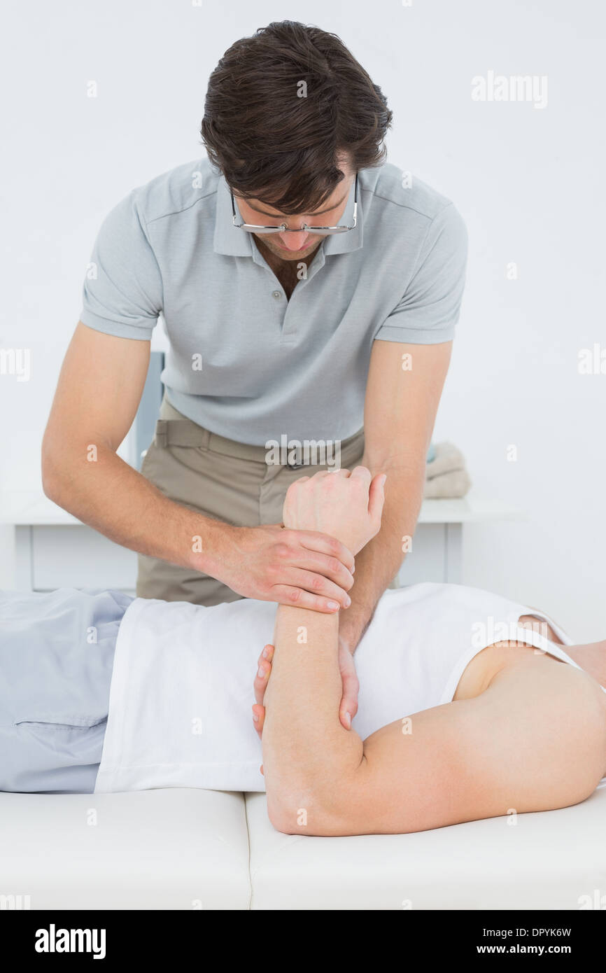 Male doctor examining a patients hand - Stock Photo