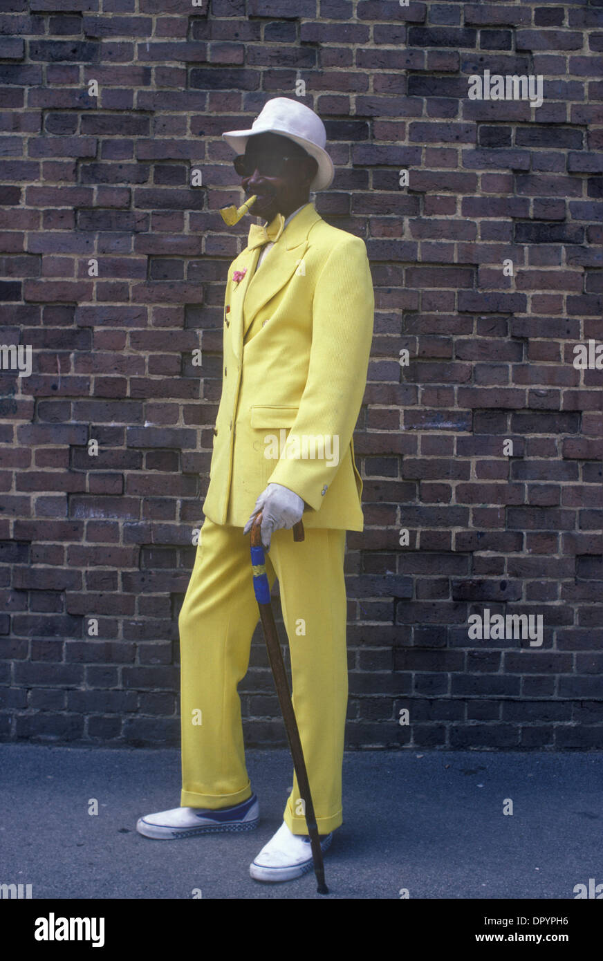 Dandy male wearing a yellow suit and smoking a yellow pipe. London Uk. HOMER SYKES - Stock Image