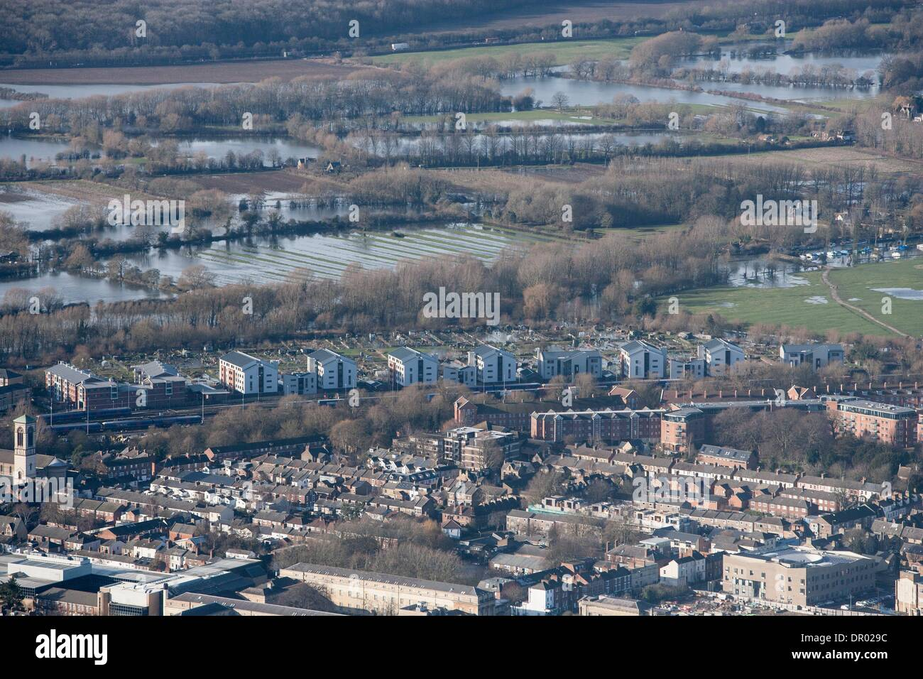 Oxford, UK. 14th January 2014. The  Thames, Oxford in  flood .  View  North towards Binsey  and the southern edge of  Portmeadow. a natural flood plain.  The controversial University buildings  of Roger Dudman Way  can  be seen ( centre )  along railway lines. Credit:  adrian arbib/Alamy Live News - Stock Image
