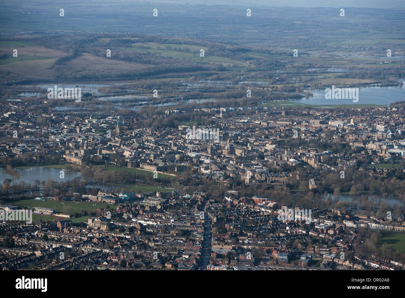 Oxford, UK. 14th January 2014. The  Thames, Oxford in  flood .  View of Oxford, West  with  Portmeadow (rhs) , a natural flood plain.  The controversial University buildings  of Roger Dudman Way  can  be seen ( centre  )  along railway lines on the southern edge of Portmeadow Credit:  adrian arbib/Alamy Live News - Stock Image