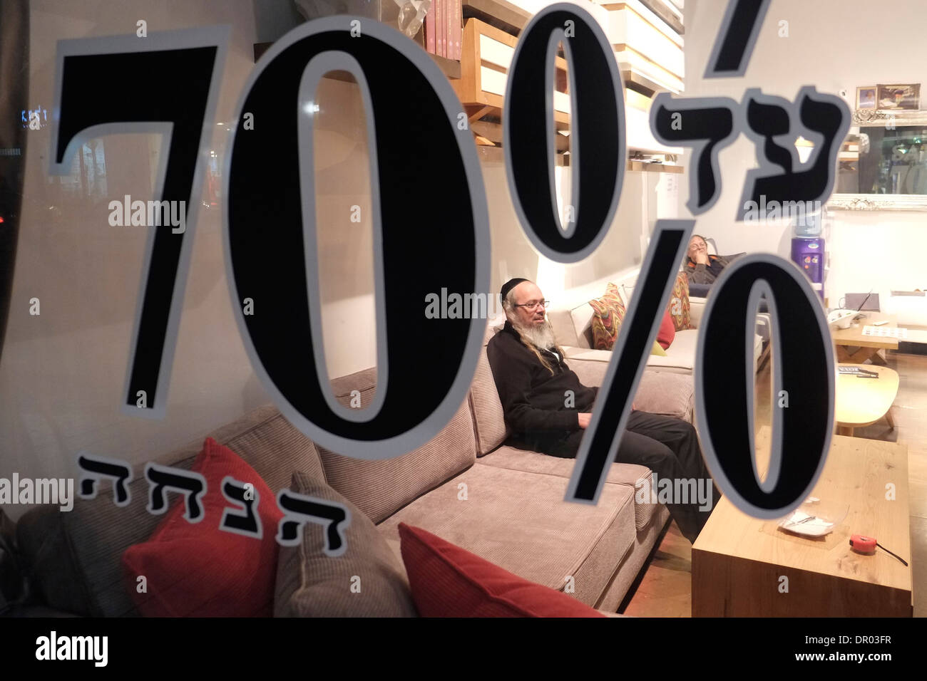 A religious Jew inside a furniture shop offering up to seventy percent reduction in Herzel Street Tel Aviv Israel - Stock Image