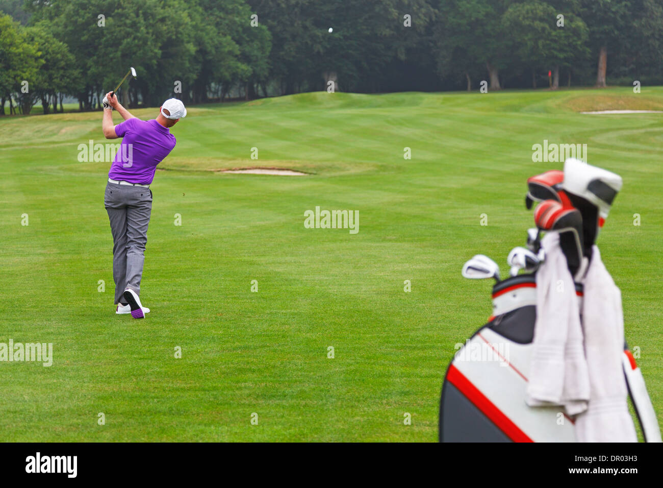 A golfer playing a mid iron fairway shot into the green on a par 4 hole, series of 3. Focus is on the golfer. - Stock Image