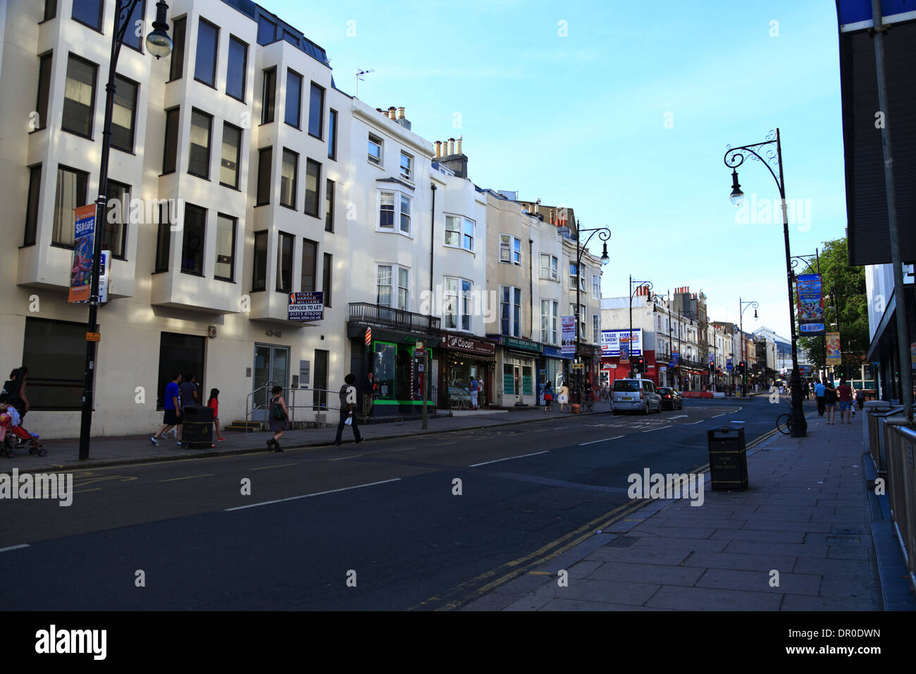 People walk past buildings in the shade along Queens Road in Brighton, East Sussex, UK, on a early summer's evening. Stock Photo