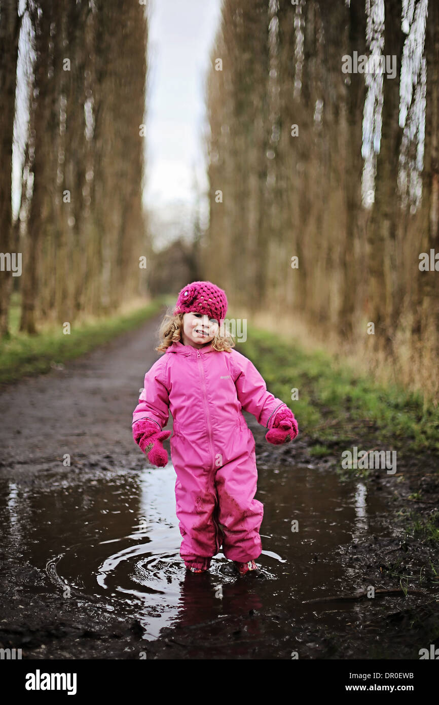 Little girl standing in puddle on tree lined path wearing pink. - Stock Image