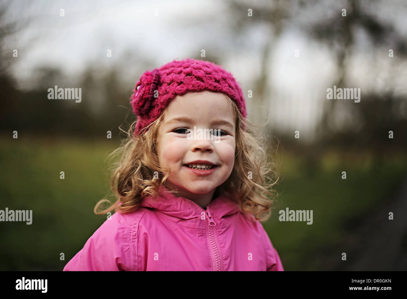 Little girl wearing pink smiling at camera - Stock Image