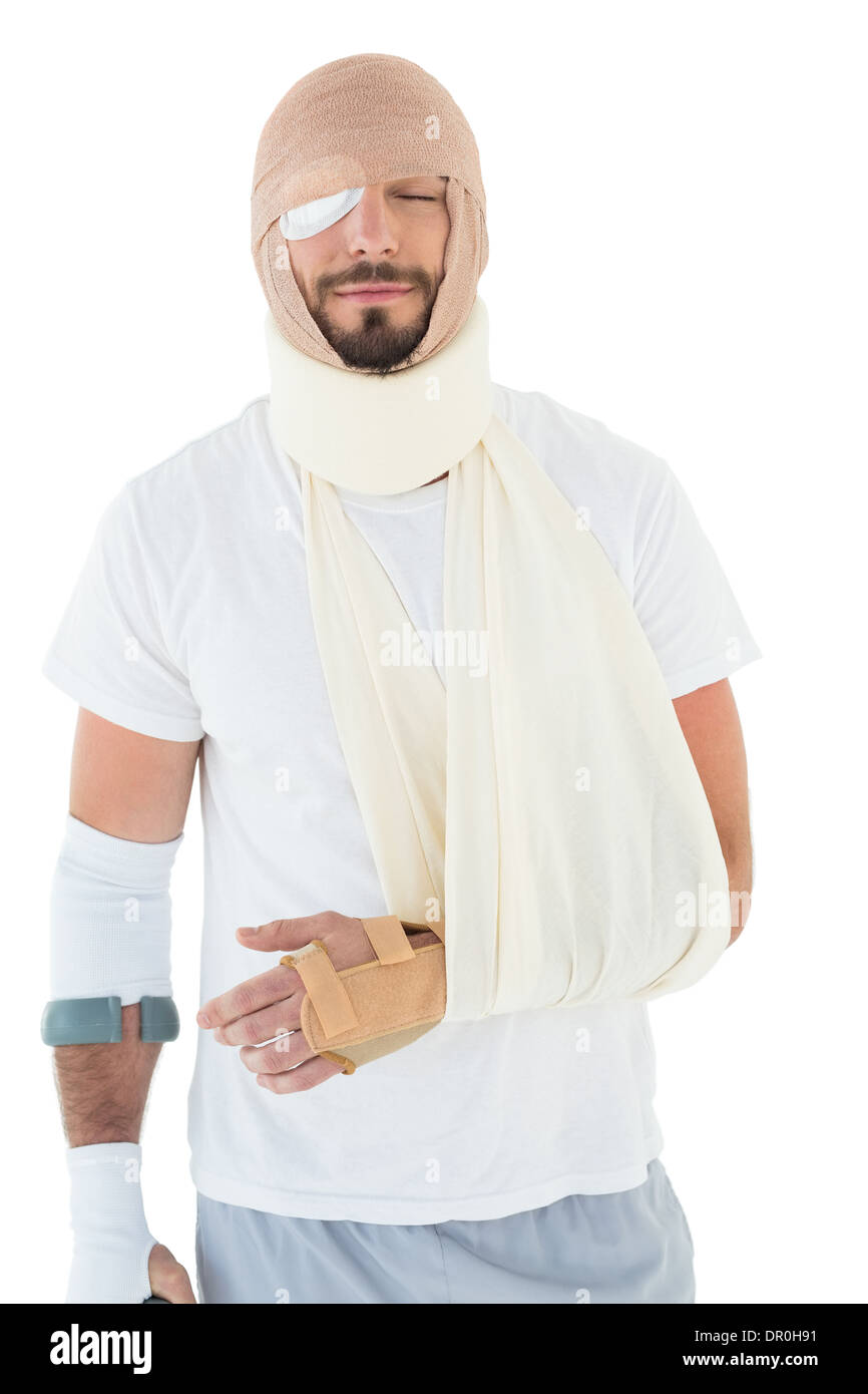 Young man with head tied up in bandage and broken hand - Stock Image