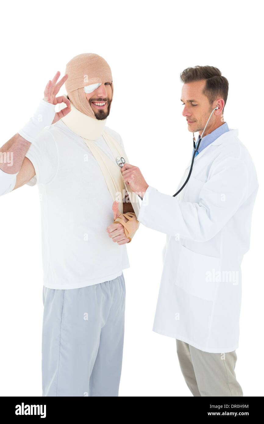 Doctor auscultating a patient tied up in bandage with stethoscope - Stock Image