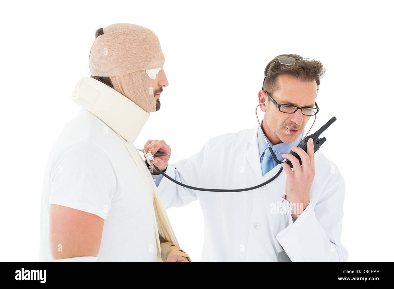 Doctor auscultating patient tied up in bandage with stethoscope - Stock Image