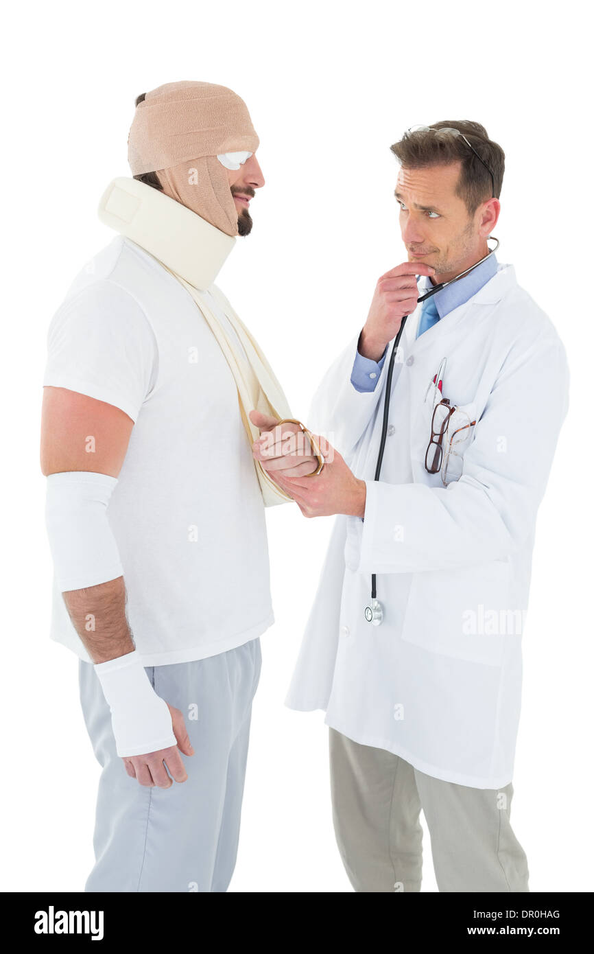 Doctor looking at patient tied up in bandage - Stock Image
