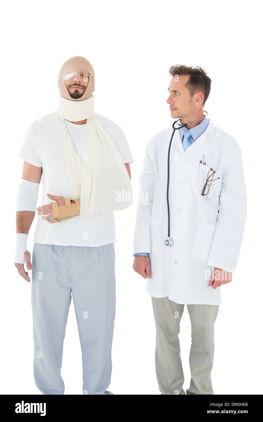 Doctor looking at a patient tied up in bandage - Stock Image