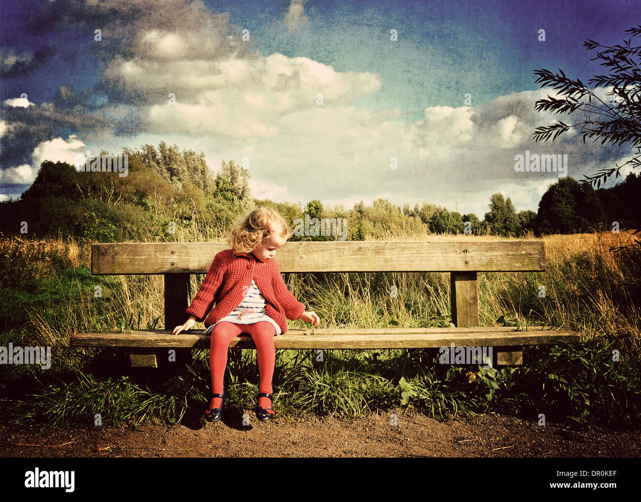 Little girl waiting on bench in countryside. - Stock Image