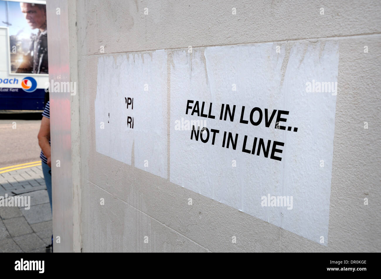 Whitstable, Kent, England, UK. Poster stuck on wall - 'Fall in Love, not in Line' - Stock Image