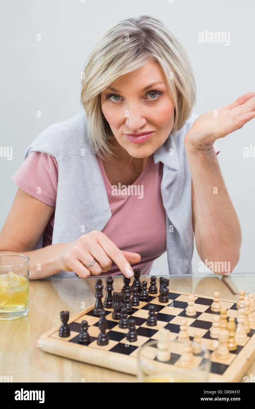 Portrait of a woman playing chess at table - Stock Image