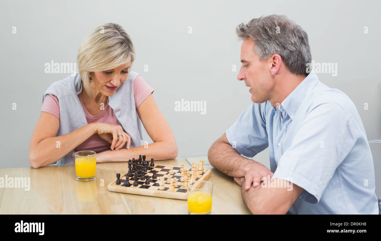 Concentrated couple playing chess - Stock Image