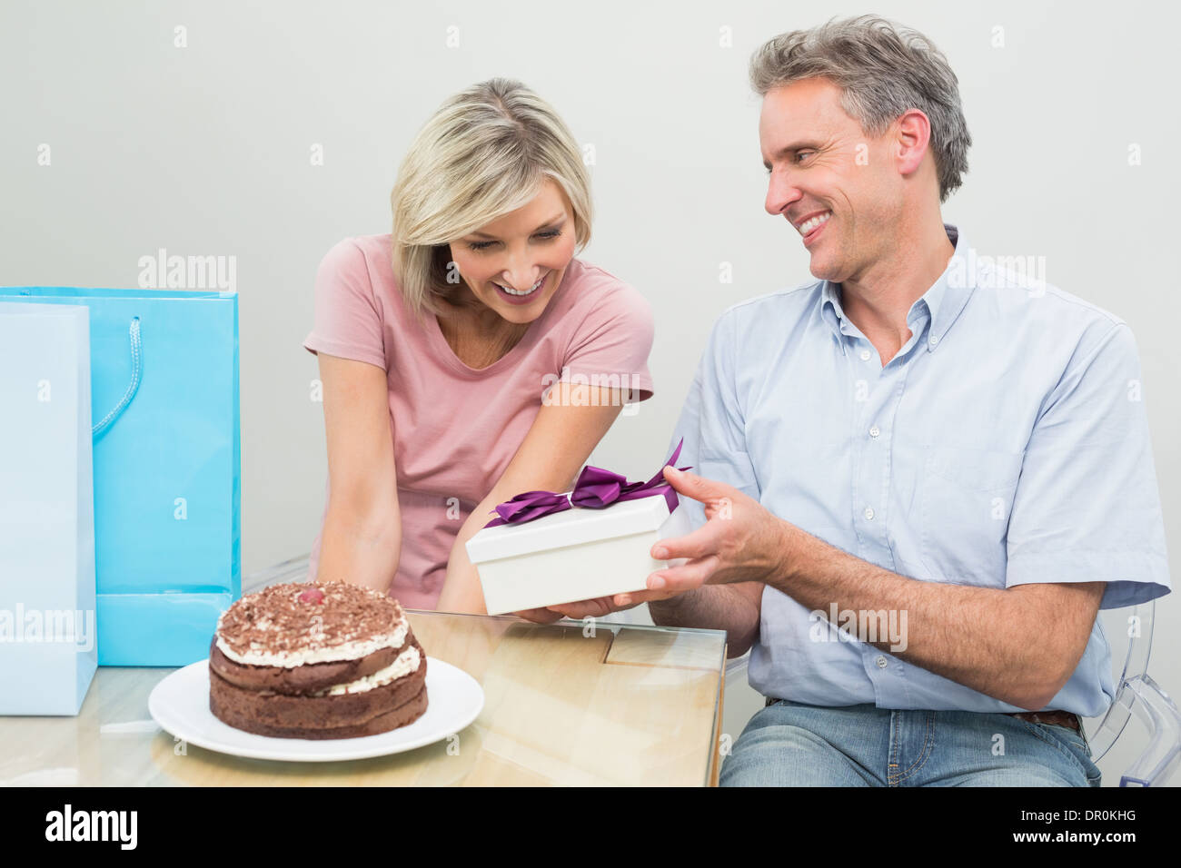 Man Giving A Happy Woman Birthday Gift Beside Cake