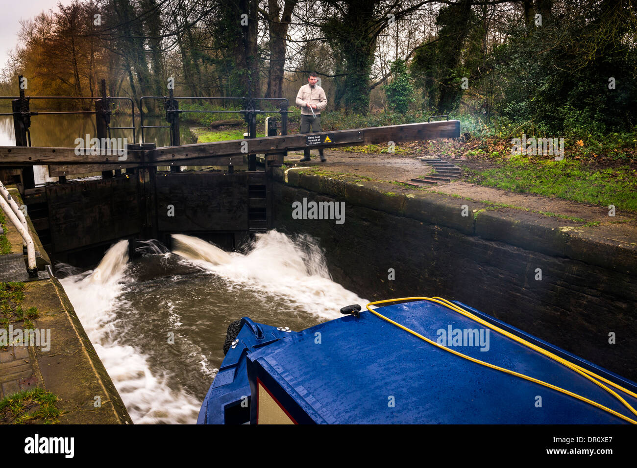 A man opens the Lock Gates on the Grand Union Canal near Watford in England. - Stock Image