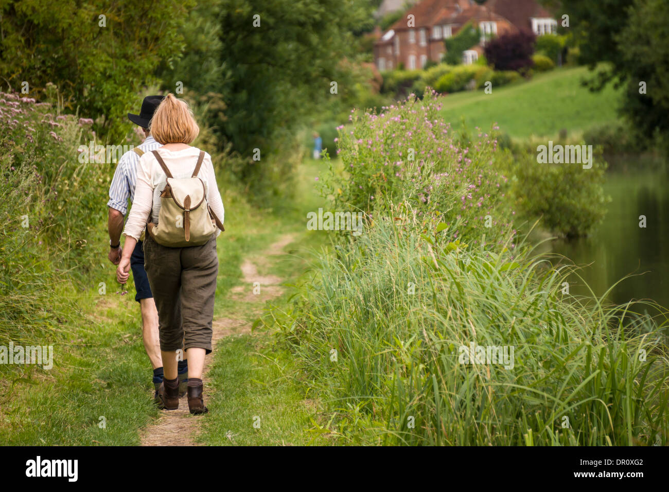 Two Ramblers walk along a canal footpath in Berkshire. - Stock Image