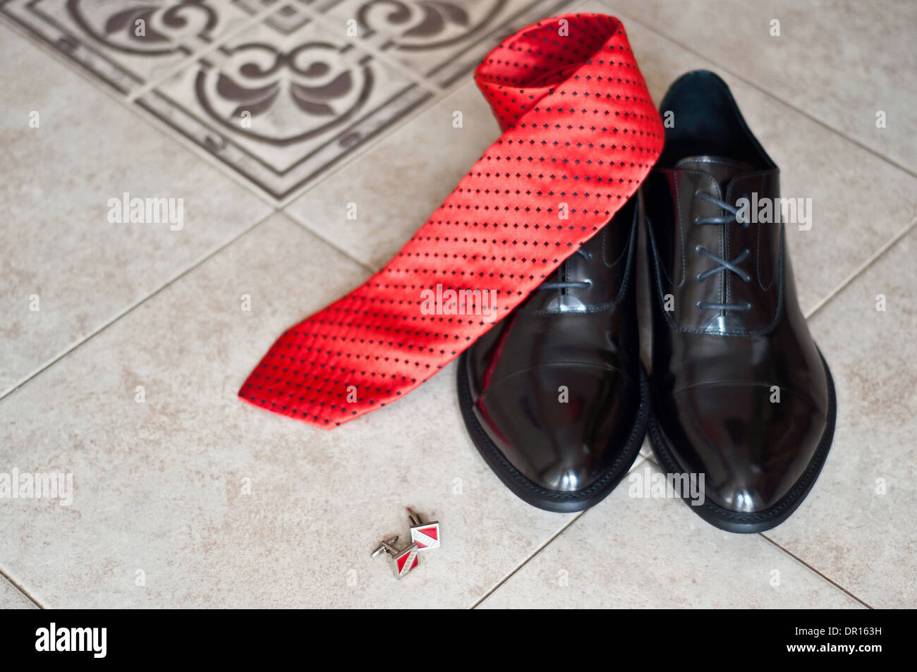 black shoes of the groom, red tie and cuff links on a floor - Stock Image
