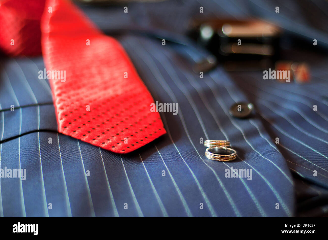 wedding rings, red tie, belt and cuff links lie on a wedding suit of the groom - Stock Image