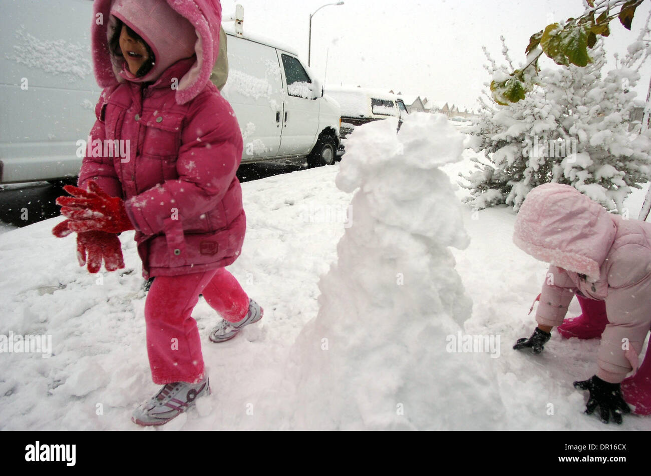 Dec 17, 2008 - Adelanto, California, USA - Snow Sisters, BRIANNA HERRERA, 4, left, SAMANTHA HERRERA, 2, and KIMBERLY HERRERA, 3, build a snowman on their Adelanto, Calif. driveway as the High Desert experienced a day of heavy snow on Wednesday, Dec. 17,  2008. (Credit Image: © Eric Reed/ZUMA Press) - Stock Image