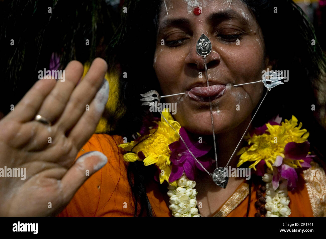 Feb 19, 2009 - Kuala Lumpur, Malaysia - A woman in tranced have a chained miniature metal lance pierced through her tounge during Thaipusam festival in Kuala Lumpur. Thaipusam is a Hindu festival celebrated mostly by the Tamil community on the full moon in the Tamil month of Thai. Pusam refers to a star that is at its highest point during the festival. The festival commemorates bot - Stock Image