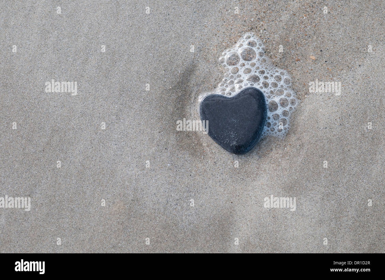heart shaped stone on wet sand, normandy, france - Stock Image