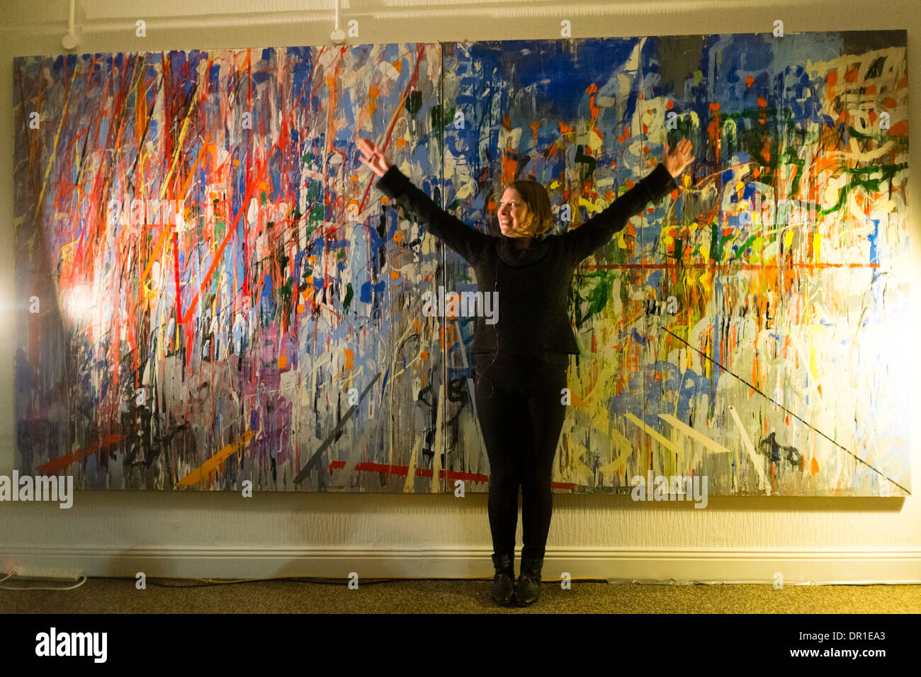 Performance Art - a woman artist performing live art in front of abstract painting a gallery UK - Stock Image