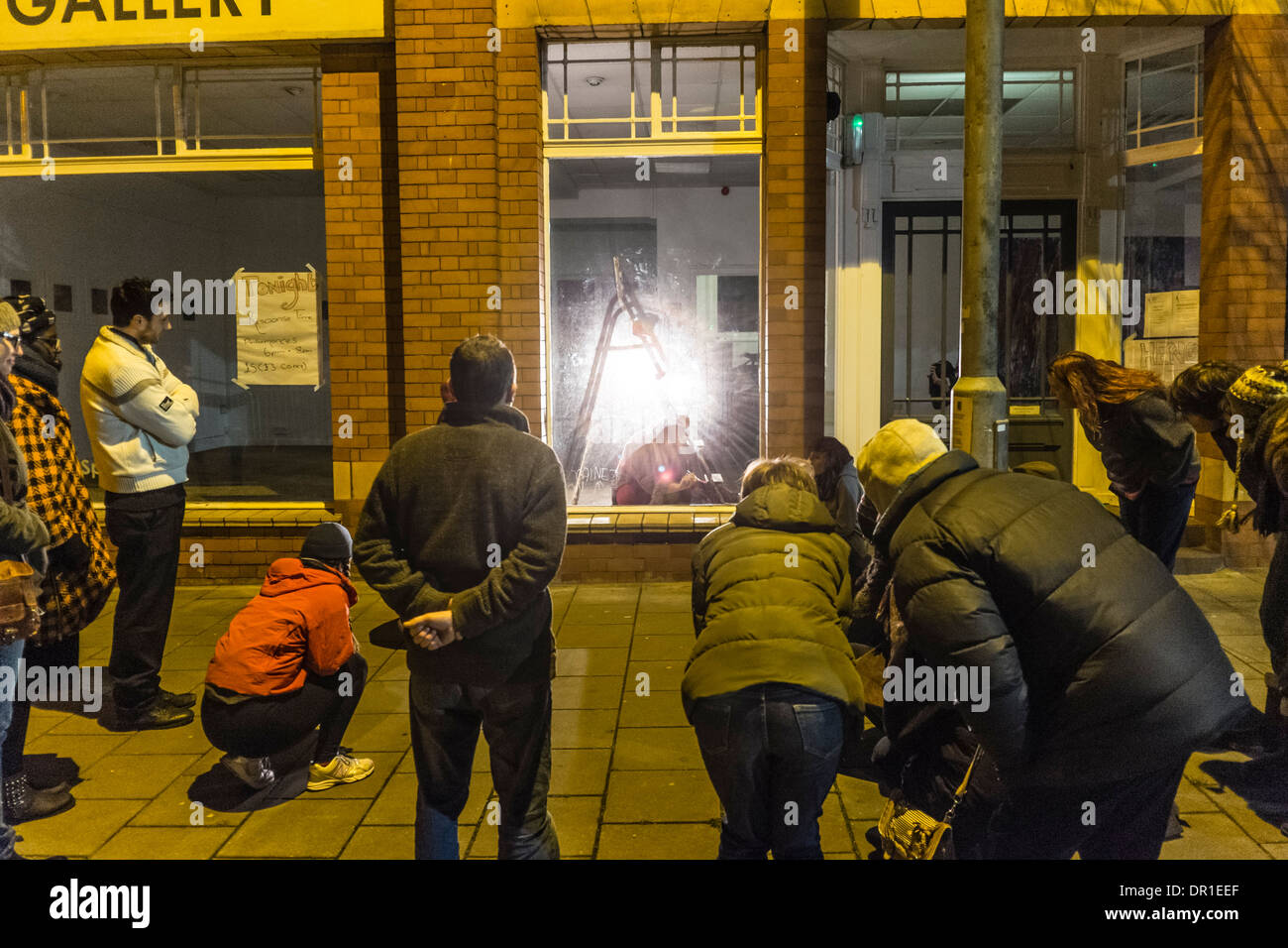 Performance Art - people outside watching a woman artist performing live art in a gallery UK - Stock Image