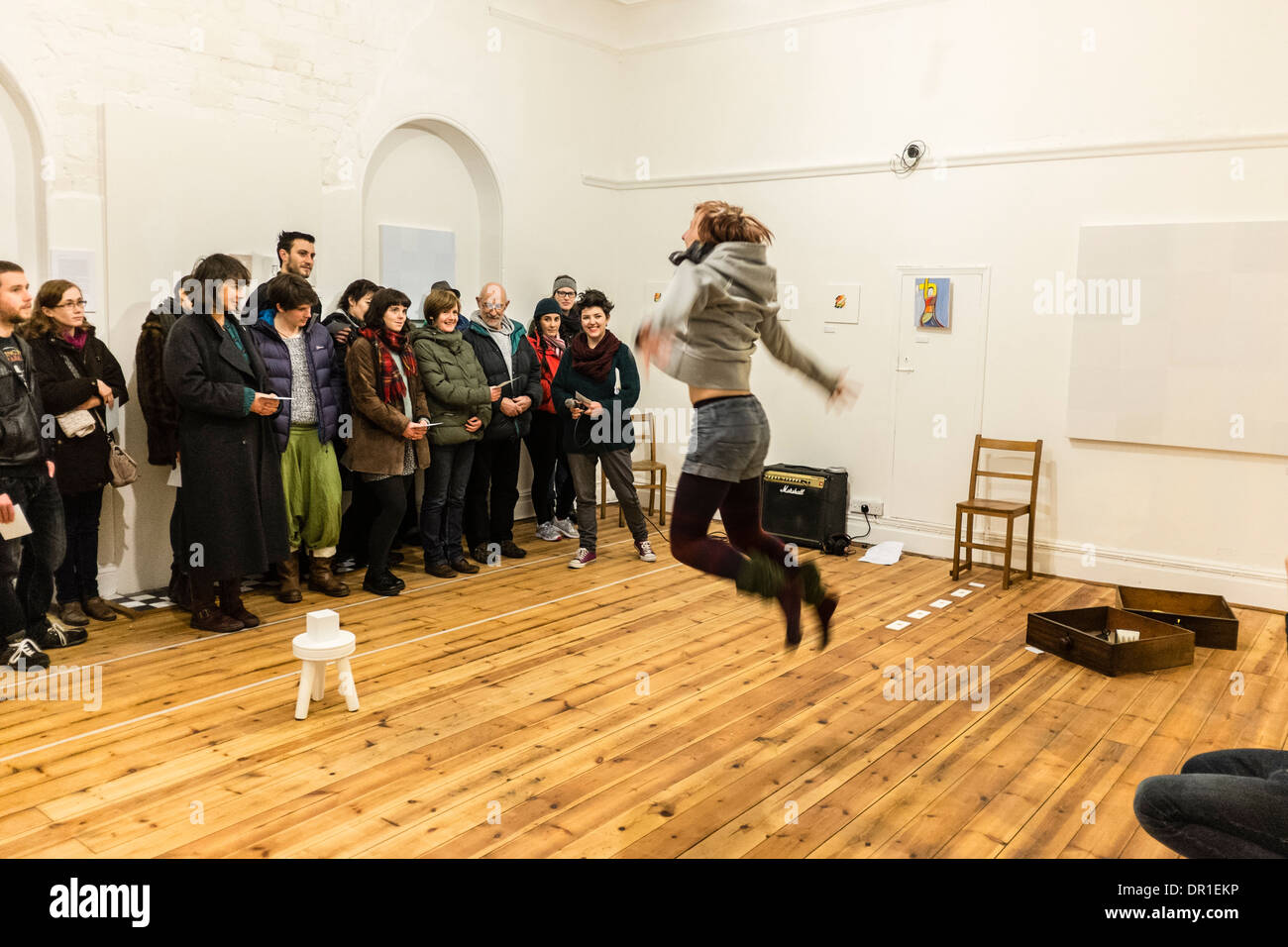 Performance Art - people watching a woman artist performing live art in a gallery UK - Stock Image