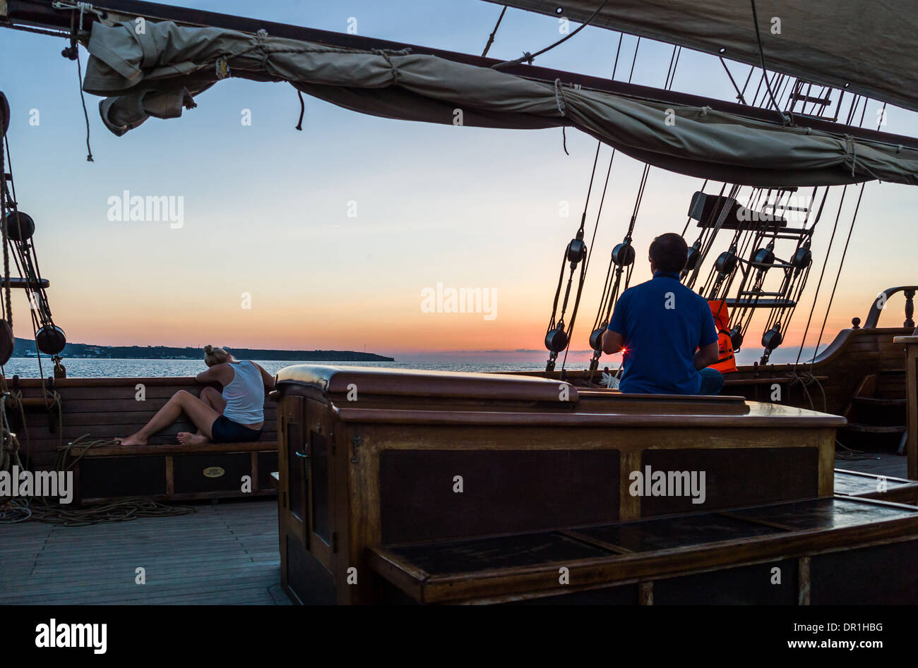 Greece, Santorini, people relaxing on a Brigantine in navigation in the Caldera sea area - Stock Image