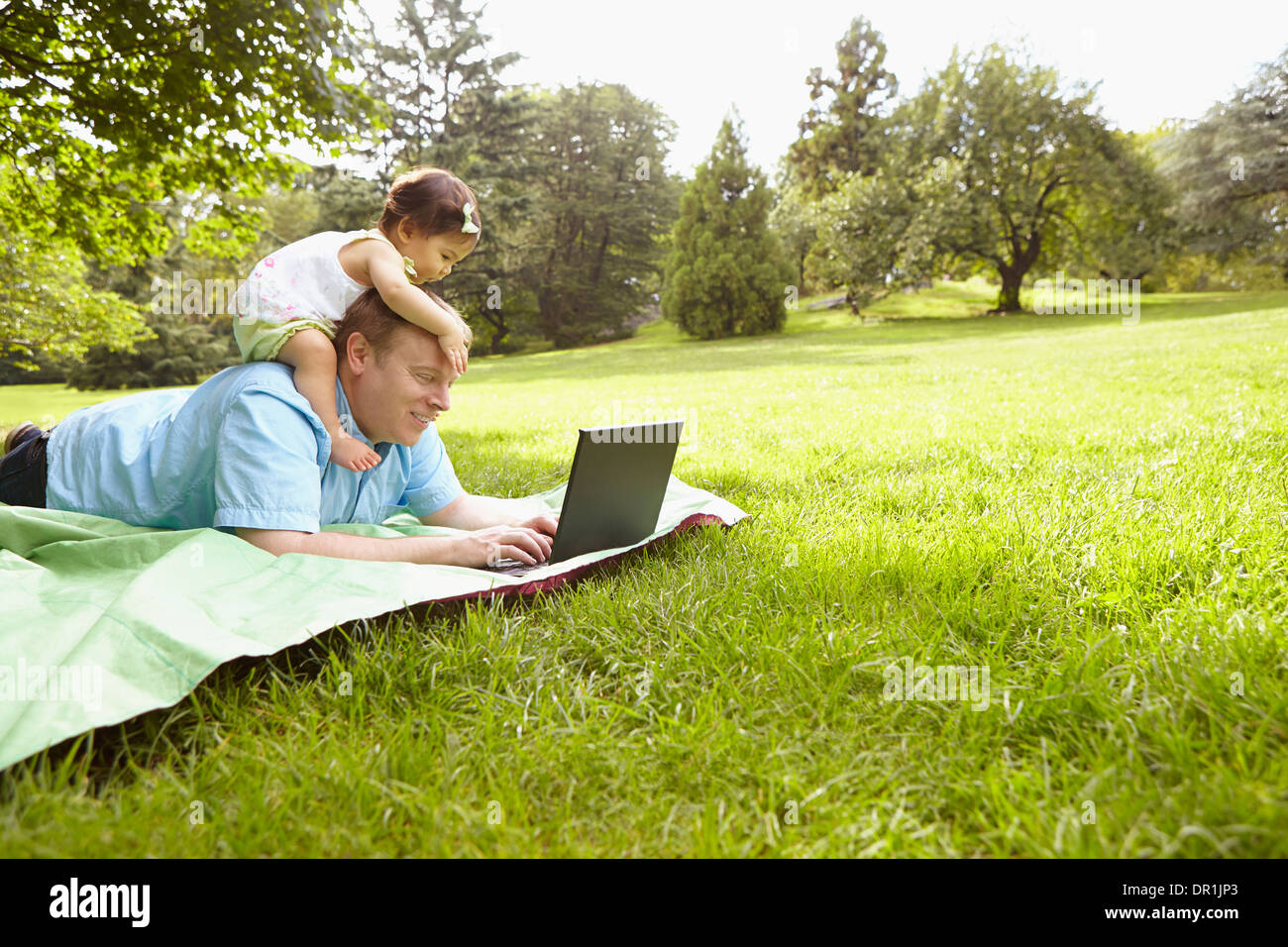 Father and baby girl using laptop in park Stock Photo
