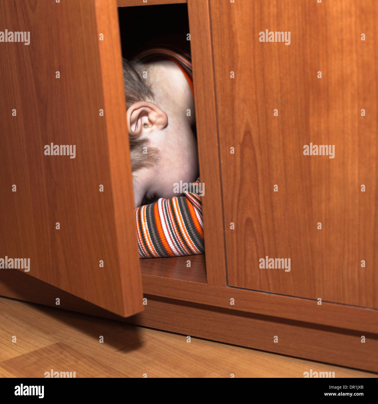 Scared child boy hiding in wardrobe - Stock Image